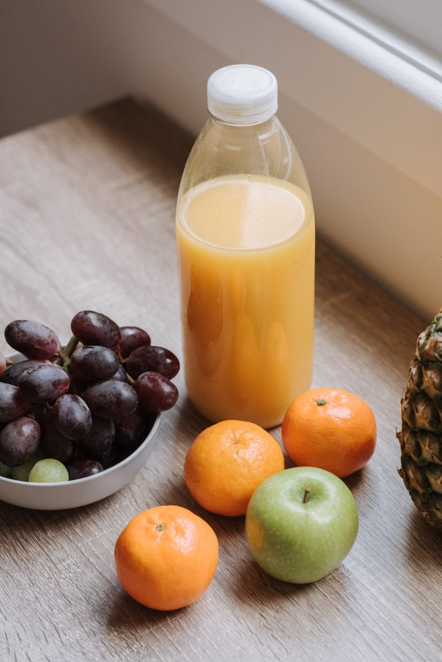 Orange Juice in Clear Glass Bottle Beside Grapes and Grapes