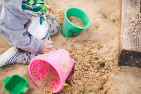 Little boy playing in the sand and buckets of sand