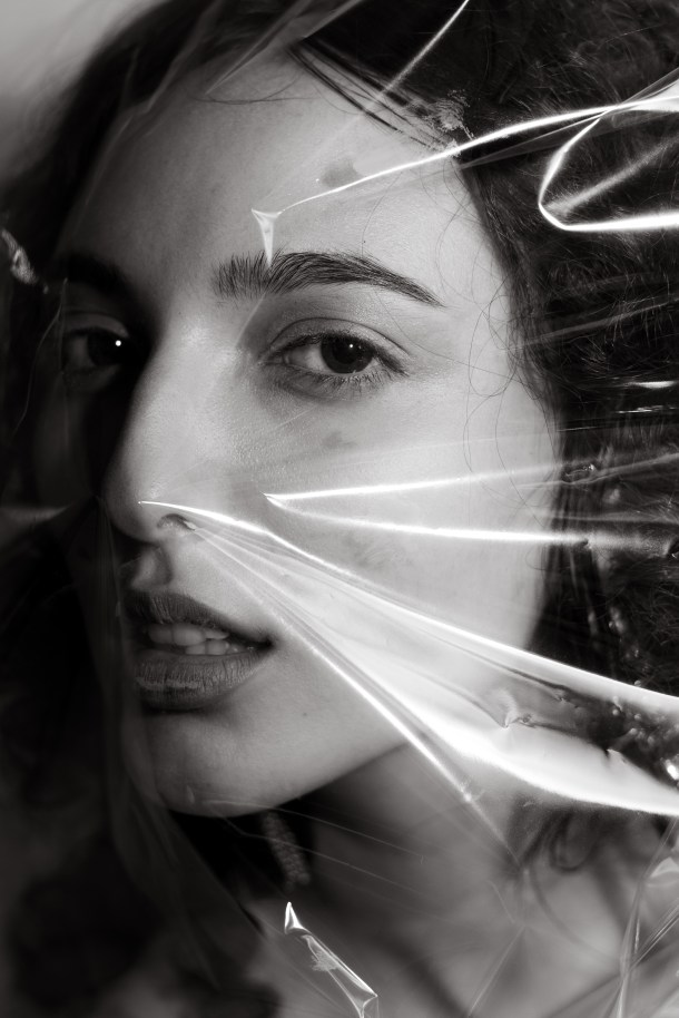 Black and white of young confident woman with cellophane wrap on face while looking at camera