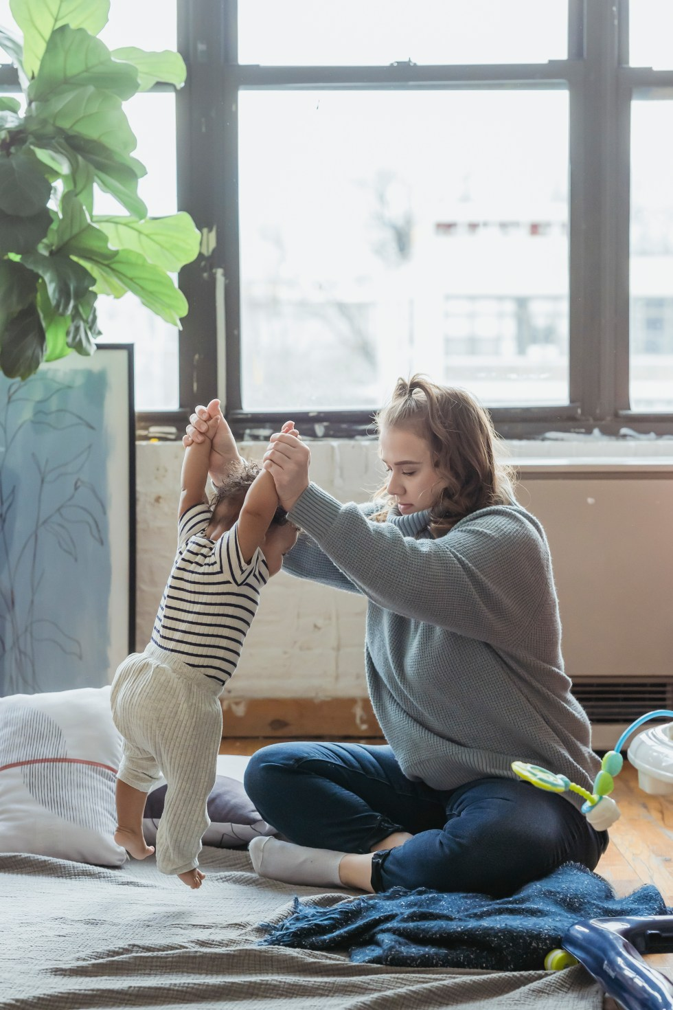 Full body positive mother in casual clothes teaching adorable toddler to walk while sitting on floor with legs crossed in light room