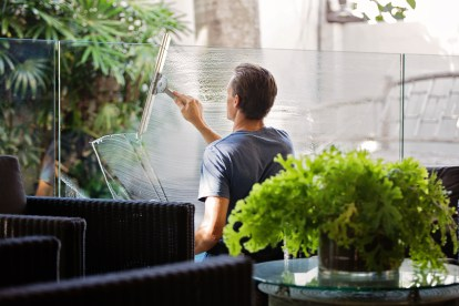 Man in Gray Shirt Cleaning Clear Glass Wall Near Sofa