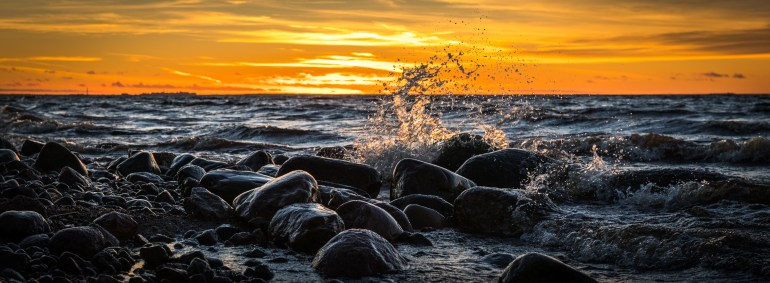 Waves Splashing at Stones on Beach during Sunset