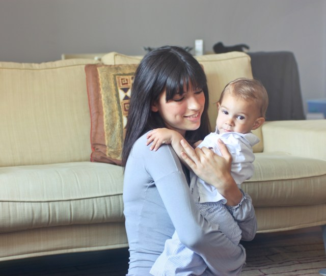 Woman In Gray Sweater Carrying Toddler In White Button Up Shirt