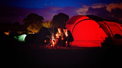 Man and Woman Sitting Beside campfire and in front of tent during Night Time