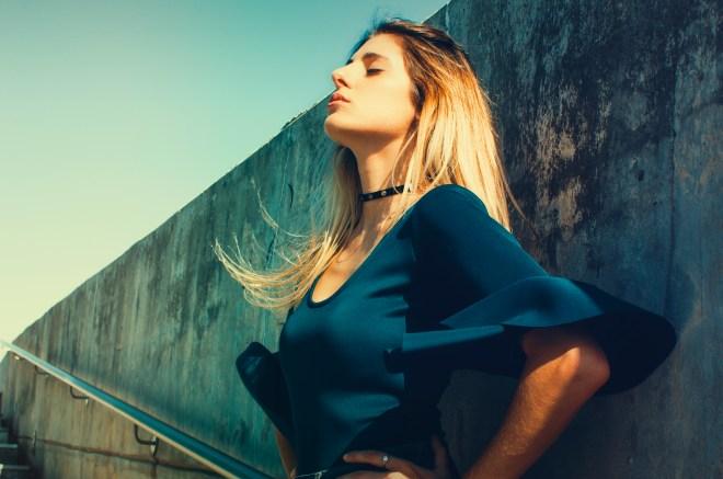 Woman Wearing Blue Scoop-neck Top Standing Near Gray Concrete Wall