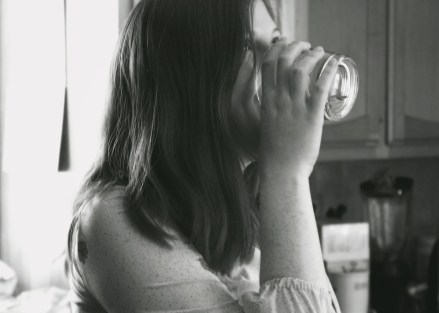 Grayscale Photo of Lady Drinking Water