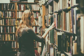 Woman in Black Long-sleeved Looking for Books in Library