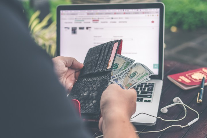 Person Holding 10 Us Dollar Banknote in Front of Gray and Black Laptop Computer
