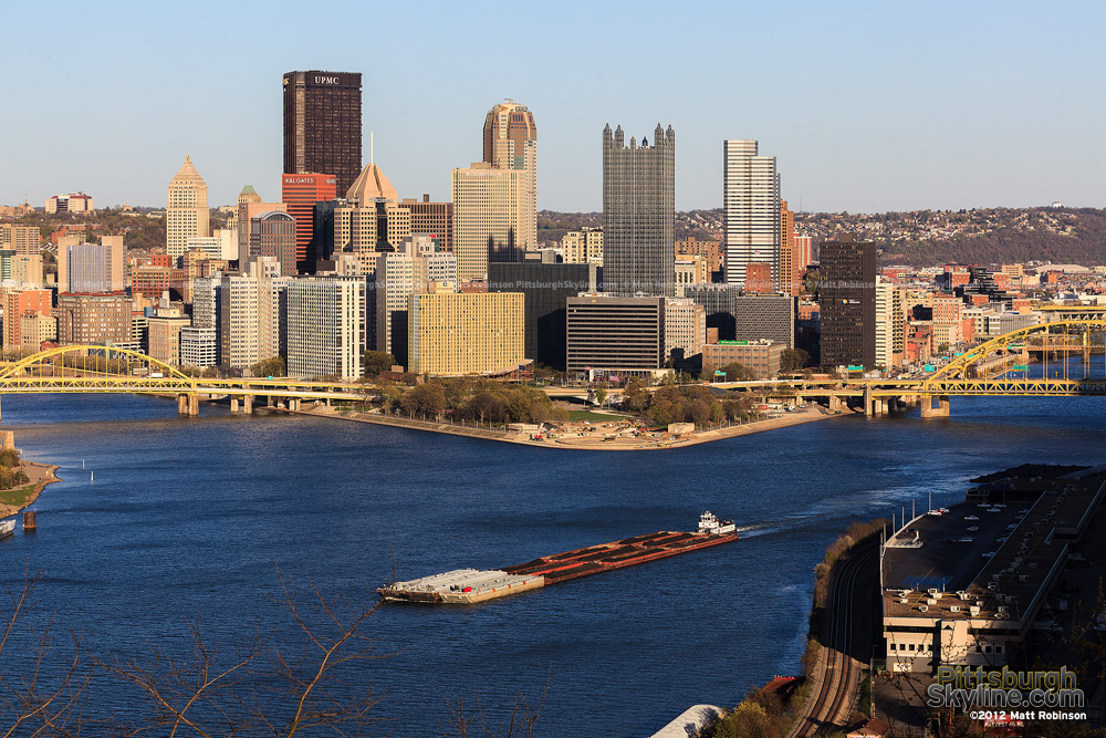 Coal barges make their way down the Ohio River with the Pittsburgh Skyline