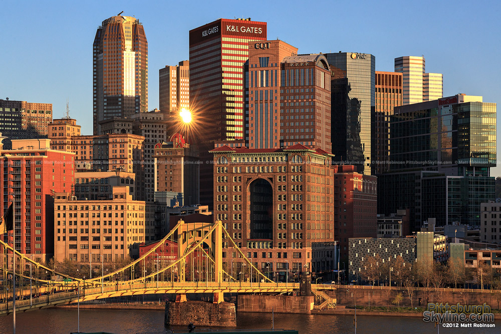 Pittsburgh buildings reflect the setting sun from PNC Park
