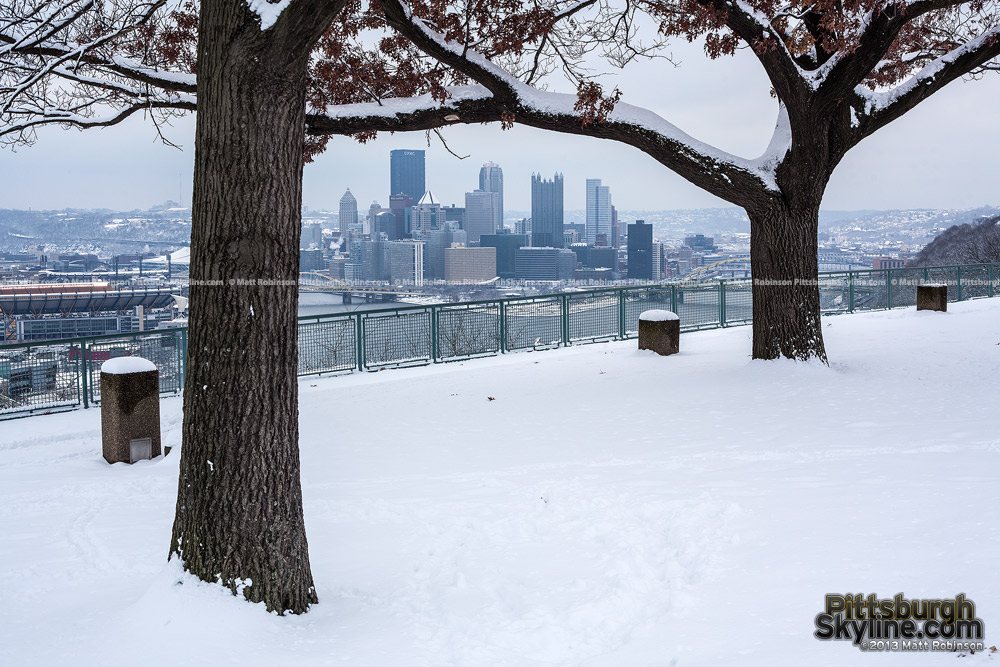 Trees frame Pittsburgh from West End Overlook with snow