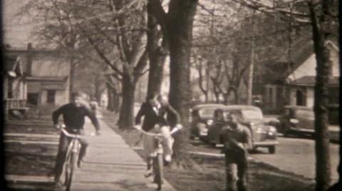 Neighborhood kids ride bikes on sidewalks 1950s vintage ...