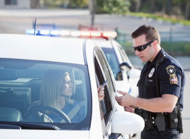 A woman getting pulled over by a police