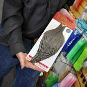 Steve Ellis, owner of the fly fishing store, Fishermen's Spot, displays a silver grade Whiting hackle that costs about $75.