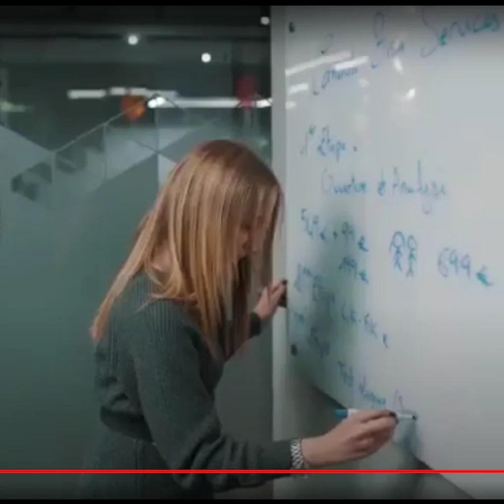 Une personne écrit sur un tableau au crayon feutre.