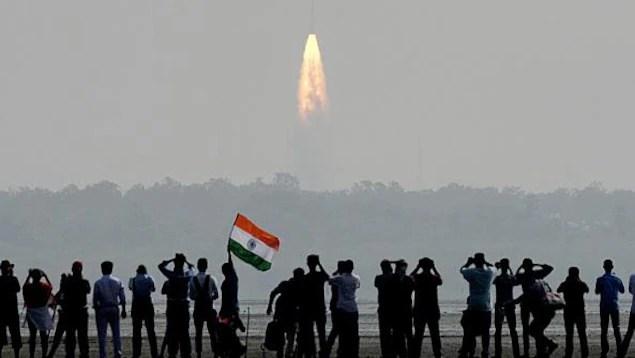 Une photo montre une foule qui observe une fusée décollée à proximité de la station spatiale de Sriharikota en Inde.