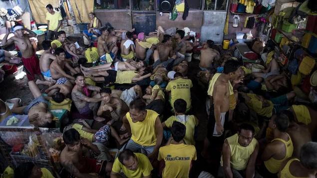 Des dizaines d'hommes revêtus de maillots jaunes s'entassent dans une grande pièce.