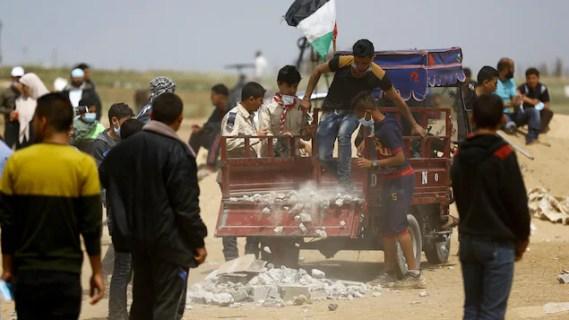 Un Palestinien vide une petite remorque remplie de débris destinés à être lancés.