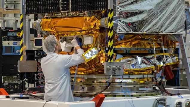 Un ingénieur de MDA, à Sainte-Anne-de-Bellevue au Québec, effectue une vérification sur un des trois satellites RADARSAT constellation qui doivent être lancés bientôt en orbite par le Canada.