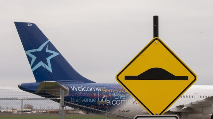 The tail of an Air Transat plane, while we see a donkey sign in the front.