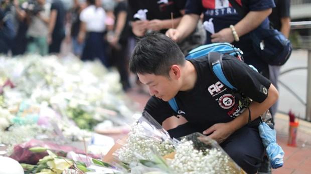 Des gens déposent des messages rendant hommage à une personne décédée tragiquement.
