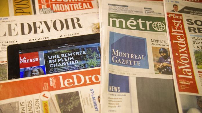 Copies of Duty, the Journal de Montréal, the Métro newspaper, the Voix de l'Est, Le Droit and an iPad showing La Presse +