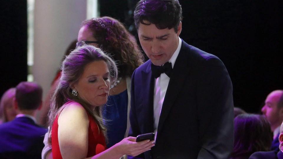 Justin Trudeau et Katie Telford regardent l'écran d'un cellulaire.