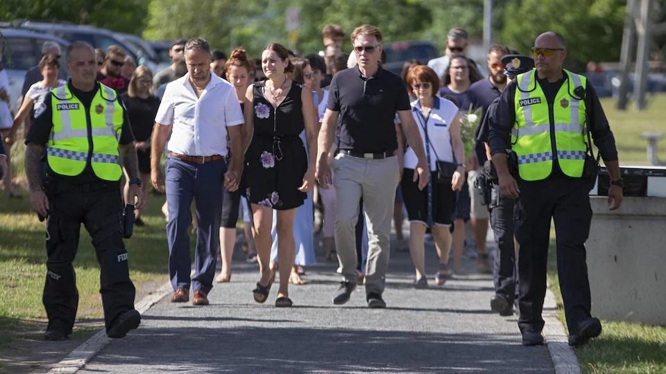Amélie Lemieux, en pleurs, marche entourée par plusieurs personnes.