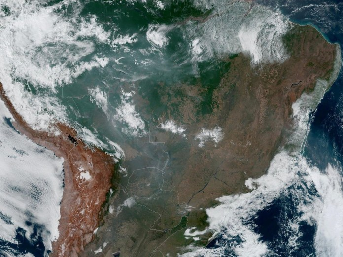 A large portion of South America, partially covered with clouds and smoke.