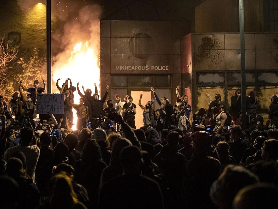 Plusieurs manifestants devant un poste de police en feu à Minneapolis, au Minnesota.
