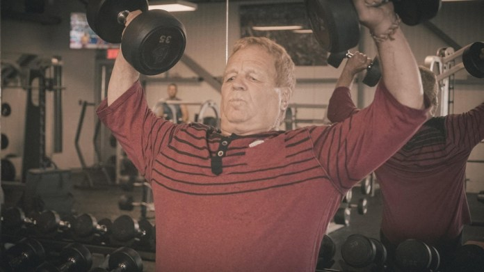 A man lifts weights in a gym