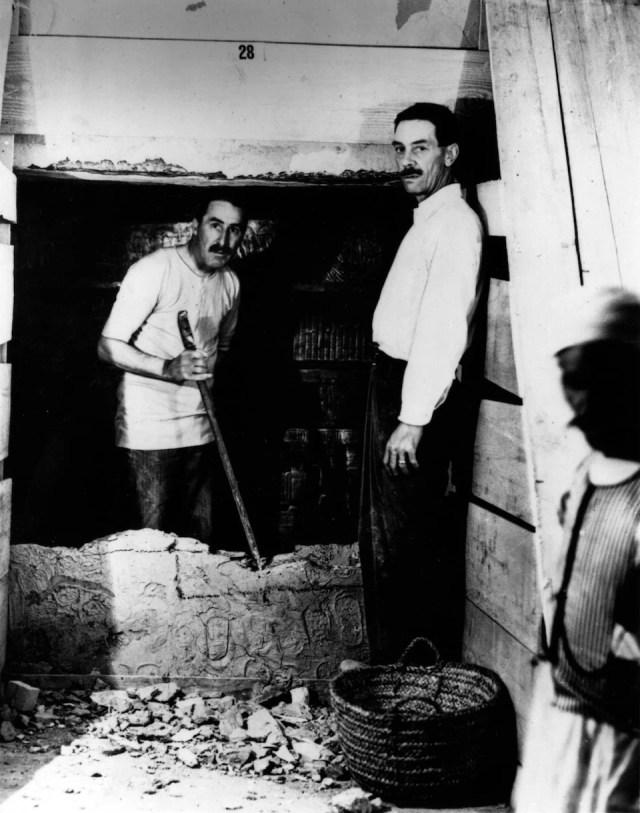 Photo en noir et blanc de deux hommes qui regardent la caméra. Ils font des travaux dans un lieu antique.