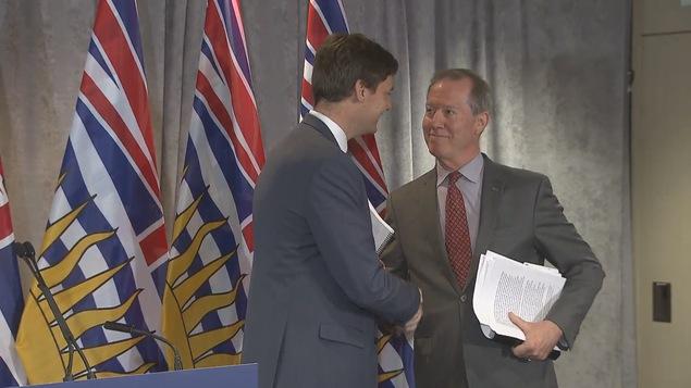 Peter German, son rapport sous le bras, serre la main de David Eby, devant les drapeaux de la province.