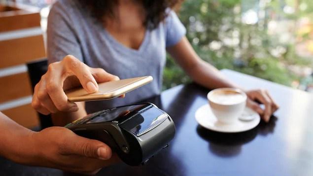 Une femme paie son cappuccino avec son téléphone intelligent.