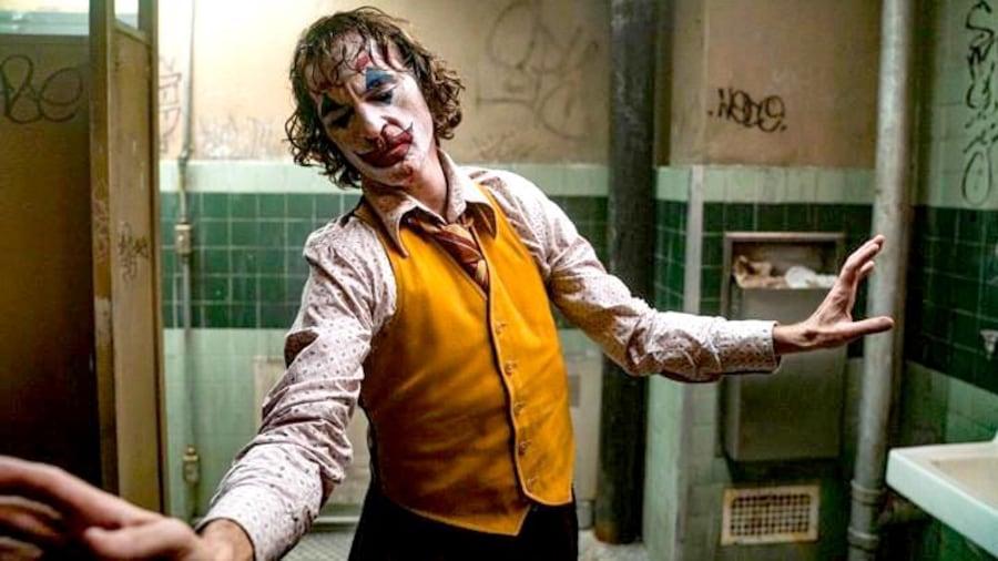Dans une salle de bains sale et délabrée, un homme maquillé en clown (Joaquin Phoenix) esquisse un mouvement de danse.