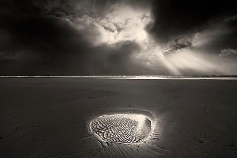 Break in the storm clouds over Llanddwyn Beach, Caernarfon Bay, Irish Sea, West Anglesey, Wales, United Kingdom