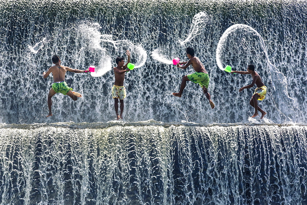 Photo of boys having a water fight in Bali