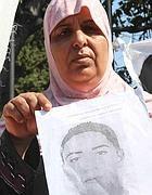 Una madre mostra la foto del figlio scomparso (Russo)