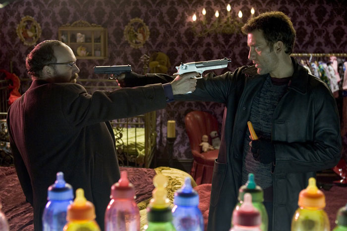 Owen and Giamatti facing each other with guns