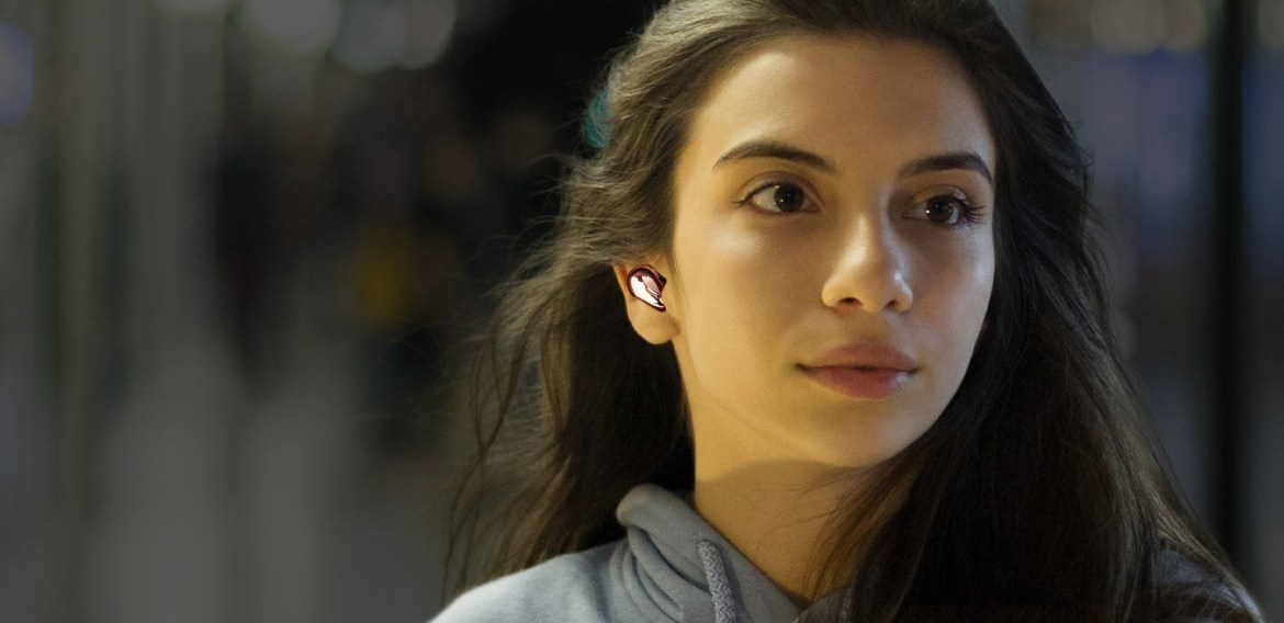 Woman standing on a busy subway platform wearing Galaxy Buds Live in Mystic Bronze with ANC off. A strong sound wave is shown underneath. Then as ANC is turned on, a close-up of the woman is seen with a dark and faded background, showing the effects of noise cancellation