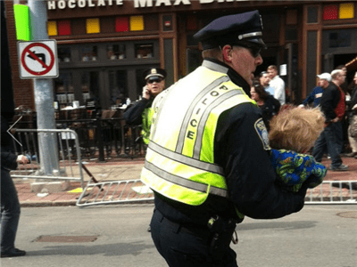 Policeman carrying a child away from bombing