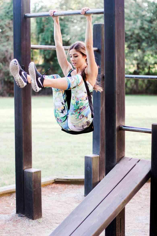 woman hanging on monkey bars