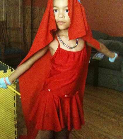 A 5 year old boy in a red dance-style frock and veil with sparkly accessories