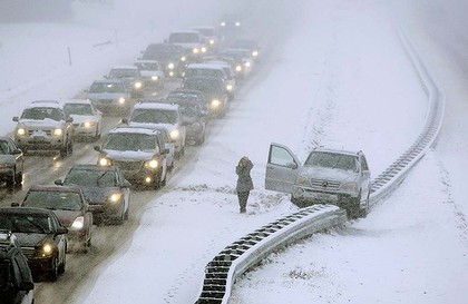 A woman  climbs out of a vehicle that ended up on a guard rail   during a snow storm in Cumberland, Maine, on Friday.