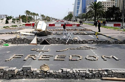 Anti-government protesters stand close to makeshift roadblocks in Manama, the capital of Bahrain, yesterday.