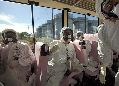 Behind glass ... reporters view the Fukushima nuclear plant damaged in March by an earthquake and tsunami.