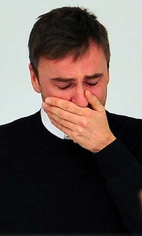 Belgian designer Raf Simons cries at the end of his final Jil Sanders show.