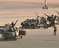 Armed militia members in military pick-up vehicles are seen on the tarmac of Tripoli international airport in this still image taken from video June 4, 2012. Clashes broke out between rival Libyan militias at Tripoli's international airport on Monday after angry gunmen drove armed pickup trucks on to the tarmac and surrounded planes, forcing the airport to cancel flights. REUTERS/Reuters TV (LIBYA - Tags: CIVIL UNREST TRANSPORT POLITICS)