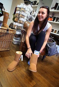 Ugg boots: 120629: Sydney Morning Herald News: 29th of June 2012: Korina  Sharpe (from the UK) tries on a pair of Ugg boots at the Ugg boot store in Sydneys Rocks district. Sales of the iconic sheepskin boot have been in decline the last two seasons due mainly to slow sales in the US market.  Photograph by James Alcock.