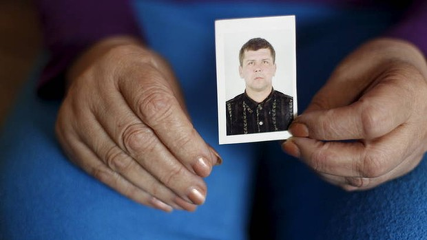 """""""Two ribs, two Achilles heels, two elbows, two eardrums, two teeth, and so on'' ... a relative holds a picture of Oleksandr Frolov, some of whose body parts were found during a raid by Ukrainian authorities."""